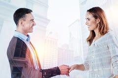 可爱的妇女与她的同事握手 免版税图库摄影
