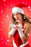 可爱的妇女作为圣诞老人吹的雪 免版税库存照片