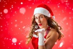 可爱的妇女作为圣诞老人吹的雪 库存照片