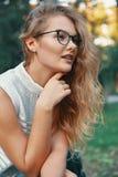 可爱的妇女佩带的玻璃,感人的下巴用手 库存图片