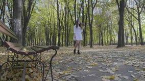 可爱的妇女佩带的白色衣裳有步行在公园和连续手指通过她的头发在一秋天天 股票录像
