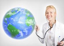 可爱的妇女医生检查的行星地球 免版税库存照片