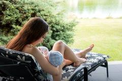 可爱的妇女和新的母亲哺乳的婴孩,当在轻便折叠躺椅的位置在比基尼泳装外面在度假时 免版税库存照片