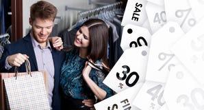 可爱的妇女和年轻人在销售中的商店 免版税库存图片