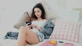 年轻可爱的妇女喝在床上的汁液 浏览互联网的深色的女孩在早餐期间,使用智能手机 库存图片