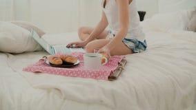 年轻可爱的妇女喝在床上的汁液 浏览互联网的深色的女孩在早餐期间,使用膝上型计算机 免版税库存照片