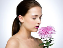 可爱的妇女嗅到的花 免版税库存照片