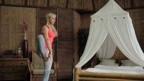 可爱的妇女在公寓屋子里实践瑜伽姿势 影视素材