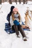 可爱的妇女在冬天森林里坐在precipic的毯子 库存图片