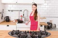 可爱的妇女在厨房里 图库摄影