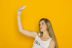 年轻可爱的妇女在她的智能手机做selfie 免版税库存图片