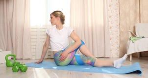 可爱的妇女在客厅做在家舒展内部的健身 图库摄影