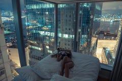 年轻可爱的妇女在床上的做自画象在晚上 库存图片