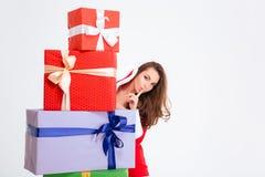 可爱的妇女在掩藏在当前箱子后的圣诞老人服装 库存图片