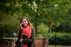 年轻可爱的妇女在秋天公园走 免版税图库摄影