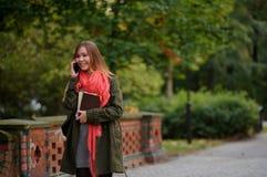 年轻可爱的妇女在秋天公园走 库存照片