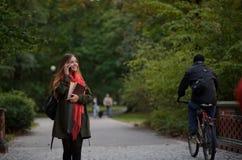 年轻可爱的妇女在秋天公园走 免版税库存图片