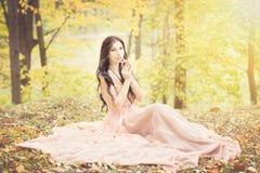 可爱的妇女在秋天,秋天在公园,庭院, 免版税库存图片