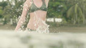 可爱的妇女在飞溅水和摆在照相机的海 微笑的女孩获得乐趣在热带棕榈树的海水 股票录像