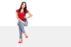 可爱的妇女坐一个空白的广告牌 库存照片