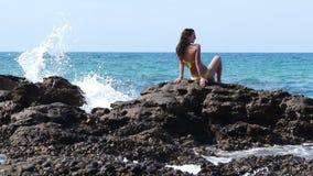 年轻可爱的妇女坐岩石 股票视频