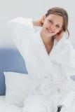 可爱的妇女坐床 免版税库存图片