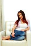 可爱的妇女坐沙发 免版税库存照片