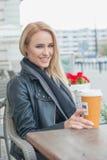 可爱的妇女坐的饮用的咖啡 库存照片
