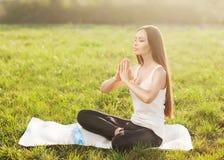 可爱的妇女实践瑜伽本质上。 免版税图库摄影