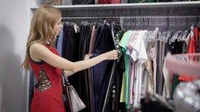 可爱的妇女寻找新的牛仔裤和长裤在精品店 股票视频