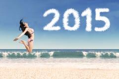 可爱的妇女庆祝在海滩的新年 库存图片