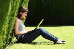 可爱的妇女愉快在有膝上型计算机的一个公园 免版税库存照片