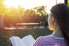 可爱的妇女户外坐读在日落的长凳一本书 回到视图 免版税图库摄影