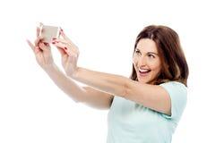 可爱的妇女拍与手机的照片 免版税库存照片