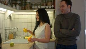可爱的妇女洗涤的果子和谈话与英俊的人在厨房里 库存图片