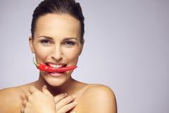 可爱的妇女用在嘴的辣椒 免版税库存照片
