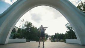 可爱的妇女站立在弹在公园前面的曲拱下小提琴 股票视频