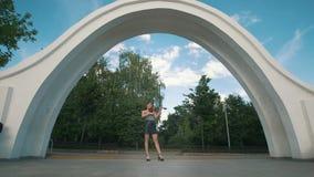 可爱的妇女站立在弹在公园前面的曲拱下小提琴 股票录像