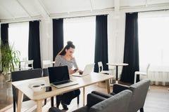 可爱的妇女自由职业者工作在膝上型计算机和智能手机的一张木书桌,当等待她共同oworker时 图库摄影