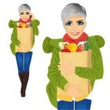 可爱的妇女运载的杂货纸袋充分健康食物,当谈话在手机时 免版税库存照片