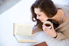 可爱的妇女阅读书和饮用的咖啡 免版税库存图片