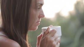 年轻可爱的妇女饮用的咖啡或茶在阳台,特写镜头 股票录像