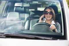 可爱的妇女驾驶和谈话在电话 免版税库存图片