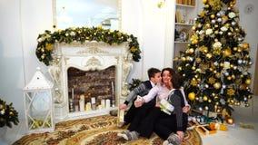 可爱的妇女,两个男孩的母亲,在有孩子的智能手机做selfie,坐地板在客厅 影视素材