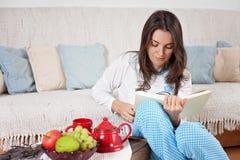 年轻可爱的妇女,在家读书,吃结果实 免版税图库摄影