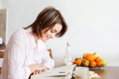 年轻可爱的妇女,在家读书,食用的果子 免版税图库摄影