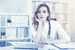 可爱的妇女医生在她的办公室,被定调子 库存图片