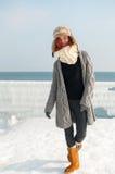 年轻可爱的妇女画象有围巾的在冬天海滩 库存照片