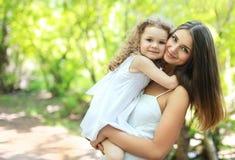 可爱的妈妈和女儿在温暖的晴朗的夏日 免版税图库摄影