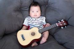 可爱的婴孩坐有微型吉他的软的沙发 小音乐家 实践孩子的音乐技能 音乐和孩子 免版税库存图片